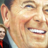 Former first lady Nancy Reagan stands next to to an image of the President Ronald Reagan commemorative postage stamp during a ceremony at the Ronald Reagan Presidential Library and Museum in Simi Valley, California in November 2004.  Nancy Reagan died on March 6, 2016, at age 94, the Reagan library said.  | REUTERS