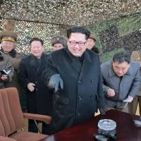 North Korean leader Kim Jong Un smiles as he attends the test launch of a new multiple-launch rocket system in this undated photo released Friday. | REUTERS