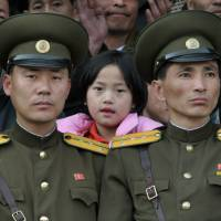 A North Korean girl and two military officers watch a World Cup soccer qualifying match at Kim Il Sung Stadium in Pyongyang. | BLOOMBERG
