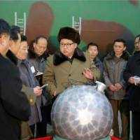 North Korean leader Kim Jong Un is shown at a missile facility inspecting a silver object that state newspaper Rodong Sinmun described as a nuclear warhead. This image is taken from a facsimile of the newspaper's front page, available on its website on Wednesday.