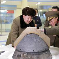 North Korean leader Kim Jong Un looks at a missile re-entry vehicle that was blasted with a jet engine, simulating the burning it would receive as it heads toward a target. The image was released Tuesday. | REUTERS