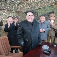 North Korean leader Kim Jong Un smiles as he guides a test fire of a new multiple launch rocket system in this undated photo released by North Korea's Korean Central News Agency (KCNA) in Pyongyang Friday. | KNCA / REUTERS
