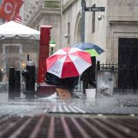 A man sits under an umbrella in the rain on Wall Street in New York on Feb. 24. | BLOOMBERG