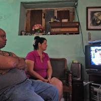 A Cuban family in Havana, with a photo of legendary Argentine-Cuban revolutionary Ernesto 'Che' Guevara on the wall, watch on TV the arrival of U.S. President Barack Obama to Cuba on Sunday for a historic three-day visit to the communist-ruled island. | AFP-JIJI
