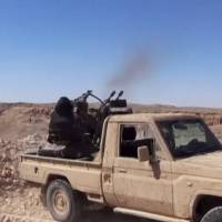 An Islamic State fighter fires an anti-aircraft gun in this still image taken from a video said to be taken on the outskirts of Palmyra and uploaded on Monday by an agency affiliated to the Islamic State, as Syrian government forces push their way into Palmyra while the army attempts to recapture the historic city from Islamic State.   SOCIAL MEDIA WEBSITE / REUTERS