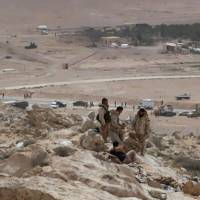 In this photo released by the Syrian official news agency SANA, Syrian government soldiers gather on a hill at the entrance of Palmyra, central Syria, Thursday.   SANA VIA AP