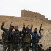 Syrian pro-government forces stand near the Palmyra citadel on Saturday during a military operation to retake the ancient city from the Islamic State group. | AFP-JIJI