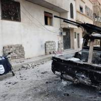 In this photo released Sunday by the Syrian official news agency SANA, a burned vehicle with machine gun is seen next to a motorcycle draped with the Islamic State group flag in the ancient city of Palmyra, central Syria. | SANA VIA AP