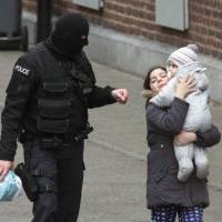 Police evacuate a woman and a small child in the Molenbeek neighborhood of Brussels on Friday after a raid that captured Salah Abdeslam, the main fugitive in the November Paris terrorist attacks.   AP