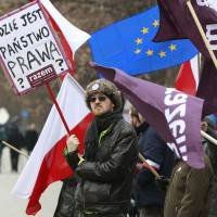 Anti-government protesters hold flags and a poster to protest the government's refusal to accept a ruling by the Constitutional Tribunal in Warsaw on Thursday. | AP