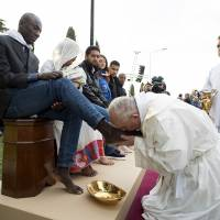 Pope Francis kisses the foot of a refugee during the foot-washing ritual at the Castelnuovo di Porto refugees center near Rome Thursday. | REUTERS / OSSERVATORE ROMANO / HANDOUT VIA REUTERS