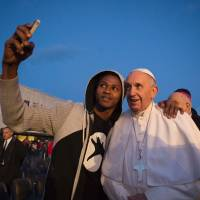 In this handout picture released by the Vatican Press Office, Pope Francis poses for a selfie with a migrant during his visit at the Castelnuovo di Porto refugees center near Rome on Thursday. Pope Francis washed the feet of 11 young asylum seekers and a worker at their reception center to highlight the need for the international community to provide shelter to refugees. | OSSERVATORE ROMANO / AFP-JIJI