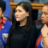 Maia Deguito (center), Rizal Commercial Banking Corp. branch manager, arrives to testify in Manila last Tuesday. | AP