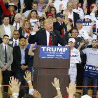 Republican presidential candidate Donald Trump speaks to the crowd Saturday asking them to take a pledge to promise to vote for him during a campaign rally, in Orlando, Florida. Trump on Tuesday defended a gesture he made at a recent rally at the request of supporters in which he raised his right hand in a way that some compared to the Nazi salute. Trump called the accusations 'ridiculous' and said his supporters wanted him to pretend that he was taking the oath of office. | AP