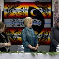 Democratic presidential candidate Hillary Clinton stands for a moment of silence for the victims of the attacks in Brusselswith Puyallup tribal members Rollen Hargrove (left) and Bill Sterud during a roundtable with Washington Tribal Leaders at Chief Leschi School in Puyallup, Washington, Tuesday. | AP