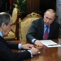 Russian President Vladimir Putin meets with Defense Minister Sergei Shoigu (unseen) and Foreign Minister Sergei Lavrov at the Kremlin in Moscow on Monday. Putin ordered the defense ministry to begin the withdrawal of Russian forces from Syria on Tuesday. | MIKHAIL KLIMENTYEV / SPUTNIK / AFP-JIJI