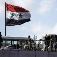 People walk near a Syrian national flag at the President bridge in Damascus on Monday. | REUTERS