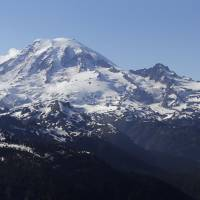 Mount Rainier is seen from a helicopter flying south of the mountain and west of Yakima, Washington, in 2013. One climber has likely died from hypothermia and exposure on Mount Rainier after he and his climbing partner were caught in a winter storm over the weekend, a spokeswoman with Mount Rainier National Park said. A Chinook helicopter crew and other rescue teams were working Monday to reach the 58-year-old man from Norway. | AP