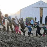 Refugee children play on a pile of gravel at the northern Greek border point of Idomeni on Friday.   AP