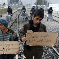 Migrants hold banners during a protest demanding the opening of the border between Greece and Macedonia in the northern Greek border station of Idomeni Wednesday. The U.N. refugee agency pulled out staff Tuesday from facilities on Lesbos and other Greek islands being used to detain refugees and migrants as an international deal with Turkey came under further strain. | AP