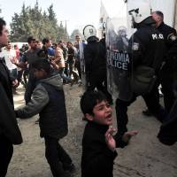 Riot police stand Tuesday in the makeshift camp at the Greek-Macedonian border, near the Greek village of Idomeni, where thousands of migrants and refugees are stranded by the Balkan border blockade. Greece will be able to process asylum claims within two weeks once a migration deal between the EU and Turkey takes full effect, a senior Greek official said. | AFP-JIJI