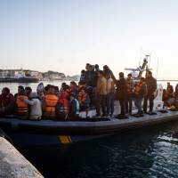 Migrants and refugees arrive aboard a Swedish Frontex patrol boat to the port of Mytilene on the Greek island of Lesbos on Tuesday. | AFP-JIJI