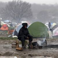 A refugee warms herself next to a bonfire under heavy rainfall in a makeshift camp for refugees and migrants at the Greek-Macedonian border near the village of Idomeni Wednesday. | REUTERS