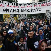 Women hold up a banner reading 'Equal rights for all refugees' as they participate with their children in a demonstration by stranded refugees and supporting groups in Athens on Wednesday. Currently some 53,000 refugees and migrants are stranded in Greece, compared to 30,000 in late February before Balkan states began shutting their borders. | AFP-JIJI