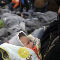 A migrant holding a baby waits to cross the Greek-Macedonian border at a makeshift camp, near the village of Idomeni, Greece, Monday. | REUTERS