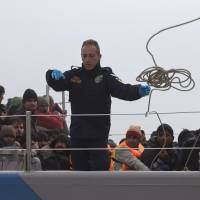 A Greek coast guardsman heaves a line to dock the ship after a rescue operation of 127 refugees and migrants off the shores of the Greek island of Lesbos Tuesday. Greece detained hundreds of refugees and migrants on its islands Monday, as officials in Athens and the European Union conceded a much-heralded agreement to send thousands of asylum-seekers back to Turkey is facing delays. | AP