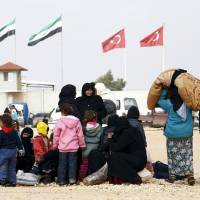 Internally displaced Syrians wait near the Bab al-Salam crossing, opposite Turkey's Kilis province, on the outskirts of the northern border town of Azaz, Syria, on Feb. 6. | REUTERS