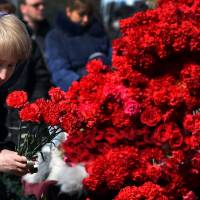 A woman lays flowers to pay a tribute to the victims of an air-crash at the Rostov-on-Don airport entrance on Sunday. | AFP-JIJI