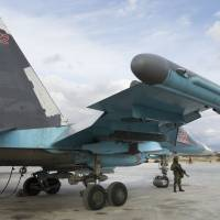 A Russian soldier stands guard next to a Su-34 bomber at Hemeimeem air base in Syria on Jan. 20. | AP