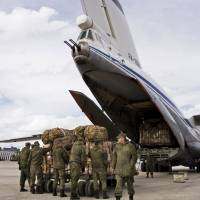 Russian air force personnel are seen loading a Syrian Il-76 plane at Russia's Hemeimeem air base in Syria in this file image from January. The Kremlin on Tuesday said the first of its warplanes have departed Syria for home. | AP