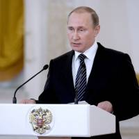 Russian President Vladimir Putin presides at a ceremony presenting state awards to military personnel who fought in Syria at the Kremlin on Thursday. He said Russia could ramp up its military presence there within 'several hours' if needed. | AFP-JIJI