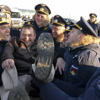 A pilot is thrown in the air by colleagues after returning from Syria at a Russian air base in Primorsko-Akhtarsk, southern Russia, on Wednesday. The Kremlin ordered a surprise partial drawdown after a five-and-a-half month air campaign. | AP