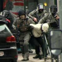 Armed police officers escort a suspect, believed to be Salah Abdeslam, the top fugitive in November's Paris terrorist attacks, to a police vehicle during a raid in the Molenbeek neighborhood of Brussels on Friday.   AP