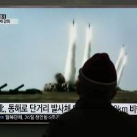 A man passing through Seoul Railway Station on Monday watches a TV screen showing file footage of a North Korean missile launch. | AP