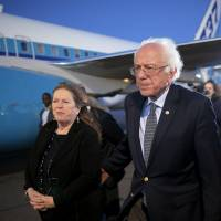 U.S. Democratic presidential candidate and U.S. Sen. Bernie Sanders and his wife, Jan,e walk away after speaking with reporters at the airport in Boston Monday. | REUTERS