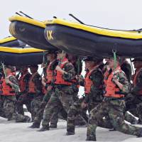 Navy SEAL trainees carry inflatable boats at the Naval Amphibious Base Coronado in Coronado, California, in 2009. | AP