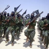 Al-Shabab fighters march with their weapons during military exercises on the outskirts of Mogadishu in February. Somalia's intelligence service cooperated with the U.S. in airstrikes that killed more than 150 al-Shabab members on Saturday, an intelligence official said Tuesday. | AP