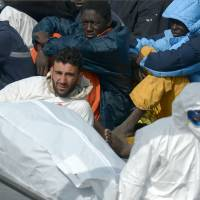 Rescuers carry the body of a victim as a man now identified as Tunisian national Mohammed Ali Malek looks on last April as he sits on a coast guard boat following a shipwreck off Libya. The preliminary hearing started in Italy of Malek's trial. He is accused of being the captain of a migrant ship that capsized, killing up to 800 people. | AFP-JIJI