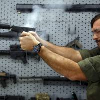 SilencerCo CEO Joshua Waldron fires a handgun with a suppressor in West Valley City, Utah, last month.   REUTERS
