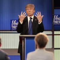 Donald Trump displays the size of his hands at the Republican presidential candidates' debate in Detroit on Thursday. | REUTERS