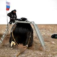 A member of a search and rescue team works at the site of landing of the Soyuz TMA-18M spacecraft, which carried International Space Station (ISS) crew members U.S. astronaut Scott Kelly, Russian cosmonauts Sergei Volkov and Mikhail Korniyenko near the town of Dzhezkazgan (Zhezkazgan), Kazakhstan, Wednesday. | KIRILL KUDRYAVTSEV / POOL / REUTERS