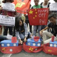 Filipino student activists set fire mock Chinese ships to protest recent island-building and alleged militarization by China off the disputed Spratlys group of islands in the South China Sea during a rally near the Malacanang presidential palace in Manila on March 3. | AP
