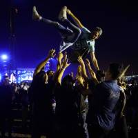 A fan is thrown aloft at  the Rolling Stones' concert in Havana on Friday. It was the first major overseas rock act to play Cuba since 1959. | AP