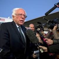Democratic presidential candidate Sen. Bernie Sanders speaks to reporters upon arrival in Boston on Monday. | AP
