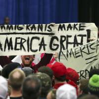 A protester holds up a sign as he disrupts a rally for Republican presidential candidate Donald Trump Tuesday, in Louisville, Kentucky. | AP