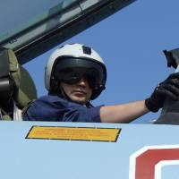 A Russian pilot prepares for take off at Hemeimeem air base in Syria on Tuesday. Russian warplanes and troops stationed at Russia's air base in Syria started leaving for home on Tuesday after a partial pullout order from President Vladimir Putin the previous day. | AP